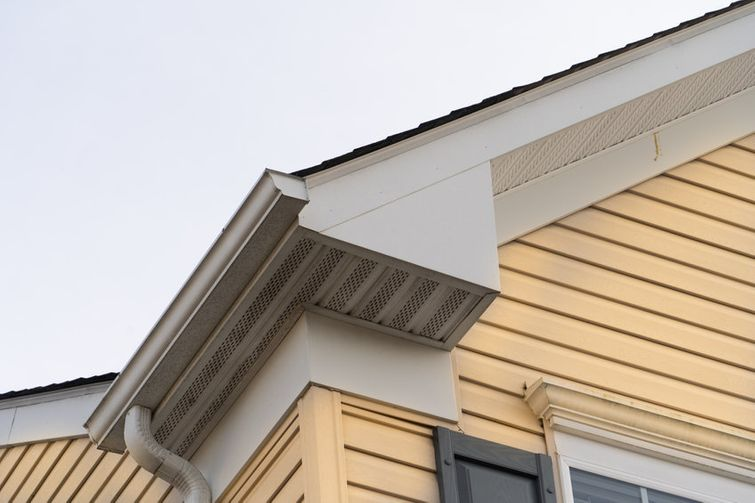 Close-up of eaves on Toronto home with yellow fiber cement siding