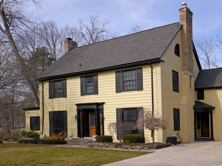 Two-storey country house with yellow aluminum siding and black accents